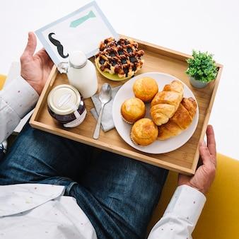 Crop man avec plateau avec de la nourriture