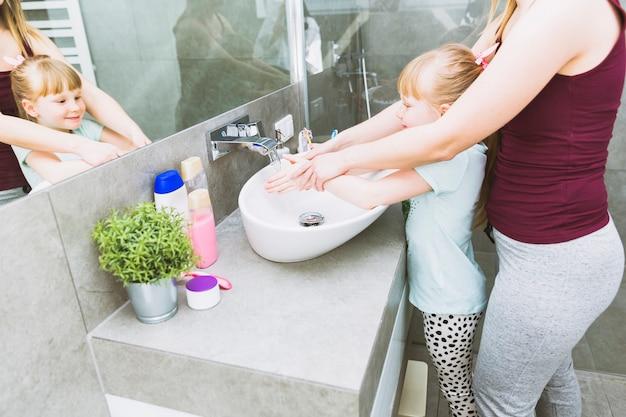 Crop mère aide sa fille à se laver les mains