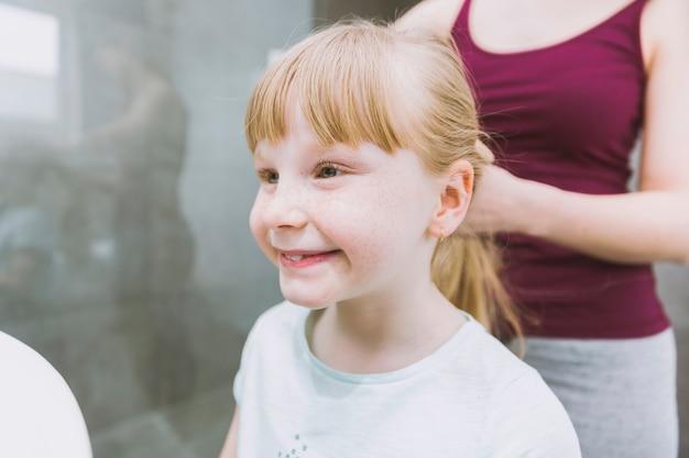 Crop mère mise en plis de la jeune fille souriante