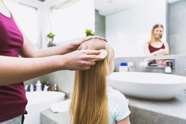 Crop mère se brosser les cheveux de la fille