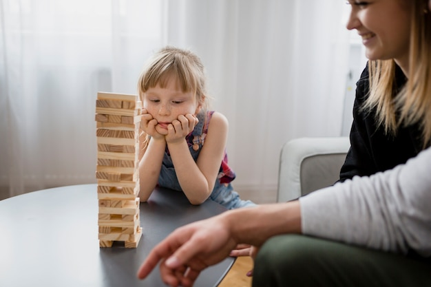 Crop parents jouant jenga avec sa fille