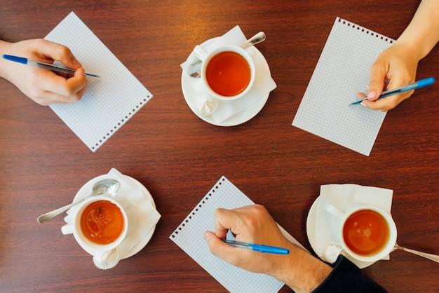 Crop people écrit sur papier parmi des tasses à thé