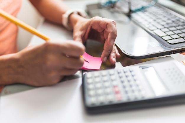 Crop personne prenant des notes au bureau