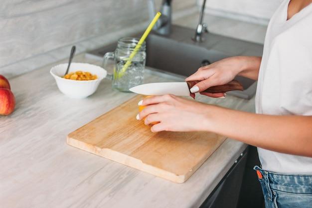 Crop photo de jeune fille mince coupe citron dans la cuisine