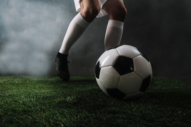 Crop soccer player balle de tir en fumée
