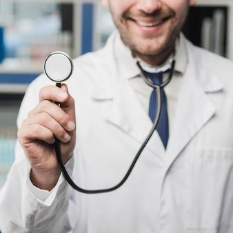 Crop souriant médecin écoutant avec stéthoscope