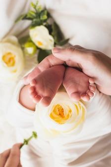 Crop tendre mère tenant des pieds de bébé