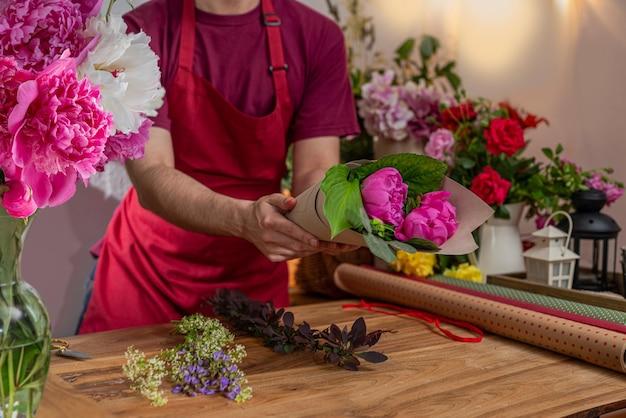 Crop view saller de fleurs vase en verre avec des pivoines en fleurs