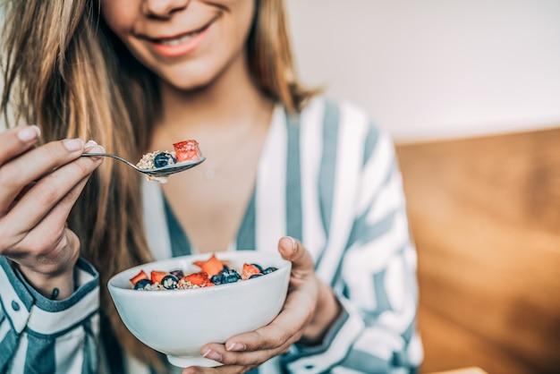 Crop woman close up manger de l'avoine et bol de fruits pour le petit déjeuner