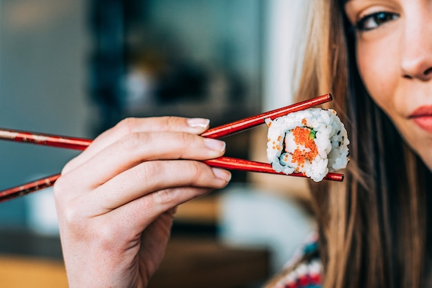 Crop woman eating sushi
