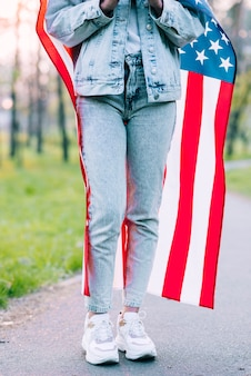 Crop woman wrapping in usa flag