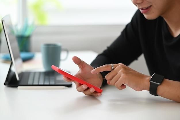 Croppe shot d'un homme graphiste est assis à son espace de travail et hans à l'aide d'un téléphone intelligent