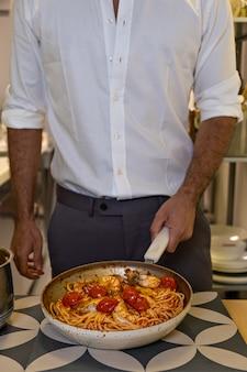 Cropped chef man in white shirt la cuisson des pâtes italiennes aux crevettes sur la casserole