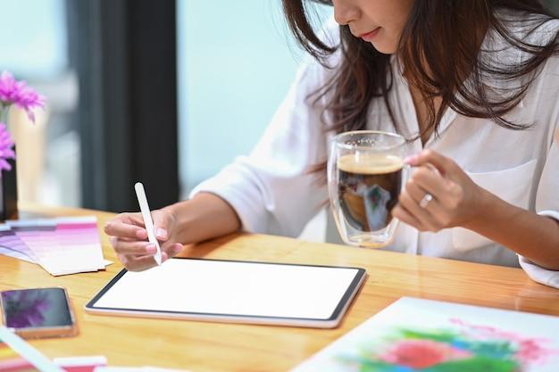 Cropped shot femme créative buvant du café et dessinant une photo sur une tablette numérique.