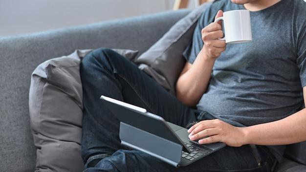 Cropped shot homme décontracté buvant du café et utilisant une tablette informatique sur un canapé.