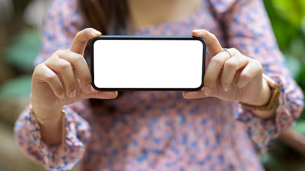 Cropped shot jeune femme montrant un écran vide maquette smartphone