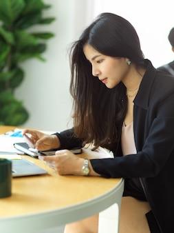 Cropped shot of businesswoman payant en ligne avec smartphone et carte de crédit dans la salle de bureau