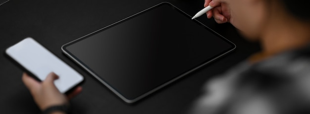 Cropped shot of female entrepreneur working with mock-up smartphone and digital tablet on black table