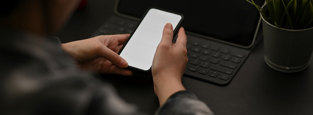 Cropped shot of female entrepreneur working with mock-up smartphone and supplies on black table