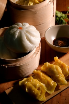 Cropped shot of home made chinese dumplings with sauce soja and bun