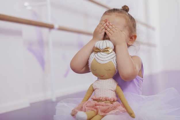 Cropped shot of a little ballerina girl playing peekaboo, copy space