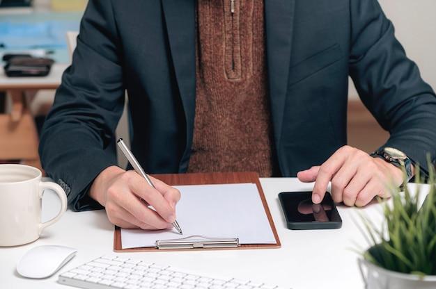 Cropped shot of man hand writing on clip board et toucher sur le smartphone à écran