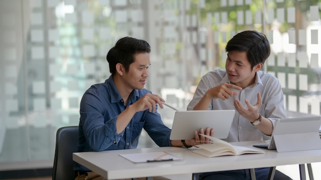Cropped shot of two businessman consulting on their work in glass wall office