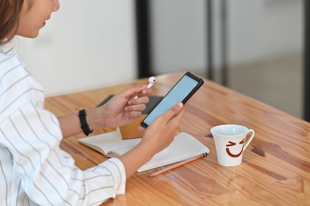 Cropped shot of a woman in rayed shirt holding white blank screen smartphone and wireless earphone in hand sitting at the wooden desk.