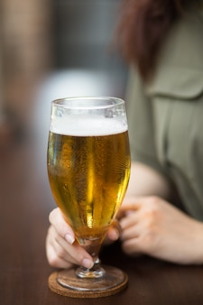 Cropped view of woman holding glass of beer