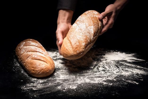 Croquant et frais. gros plan des mains du chef mans tenant une miche de pain tout en le démontrant après la cuisson.