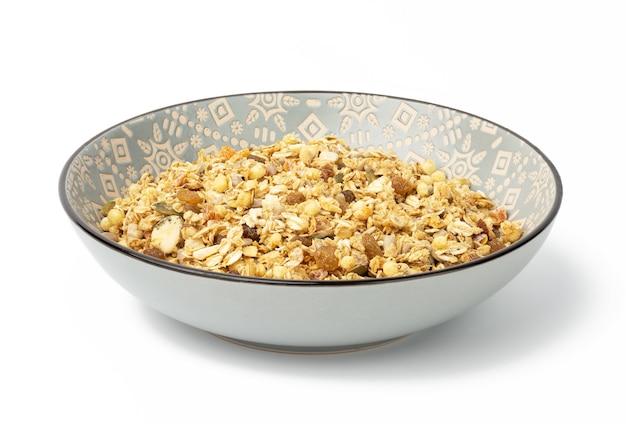 Croquants d'avoine avec des raisins secs, des graines de citrouille et des graines de tournesol dans une assiette en céramique ronde grise sur fond blanc