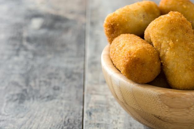 Croquetas espagnoles frites traditionnelles (croquettes) dans un bol sur fond de bois copie espace