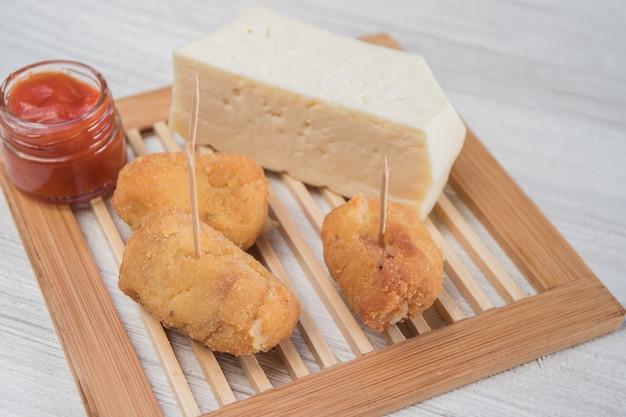 Croquettes au fromage préparées comme un tapa à prendre avec de la sauce tomate