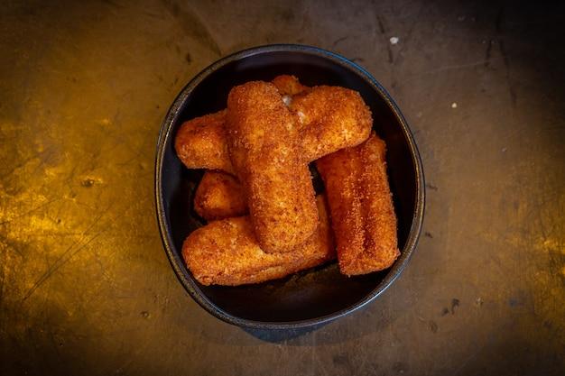 Croquettes de jambon sur fond noir et lumière orange, dans une assiette ou un bol noir