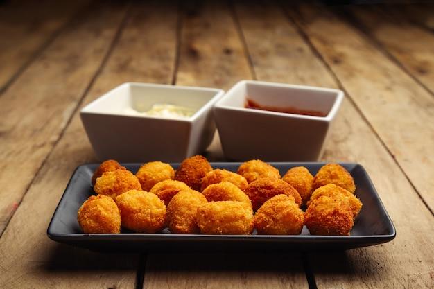 Croquettes sur plaque noire avec mayonnaise et ketchup sur table en bois