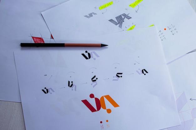 Croquis et dessins du logo imprimés sur papier. développement de la conception du logo en studio sur une table.