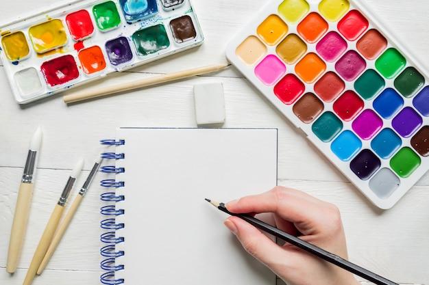 Croquis à la main féminine avant la peinture à l'aquarelle. peintures et pinceaux aquarelles, vue de dessus.