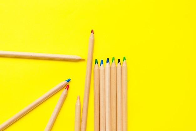 Croquis moderne serti de crayons de couleur sur fond jaune. abstrait coloré.