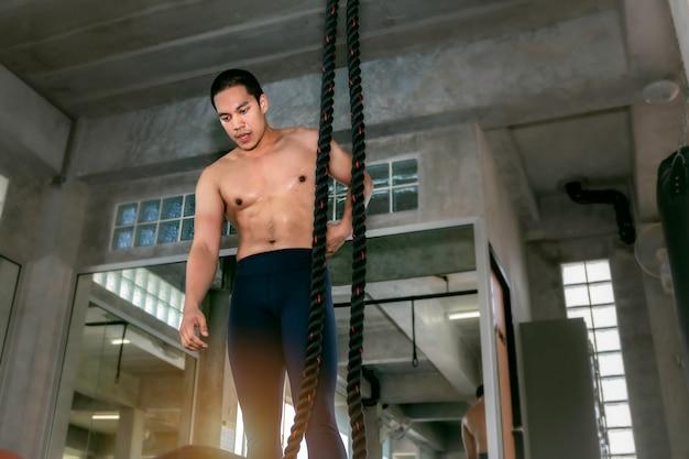 Crossfit athlétique homme asiatique formation corde escalade exercice au gymnase