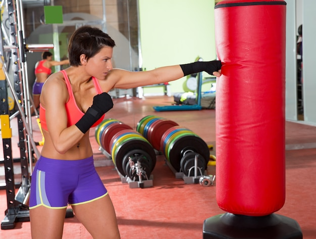 Crossfit femme boxe avec sac de boxe rouge