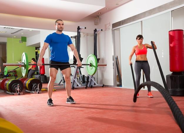 Crossfit gym haltérophilie homme femme luttant contre des cordes
