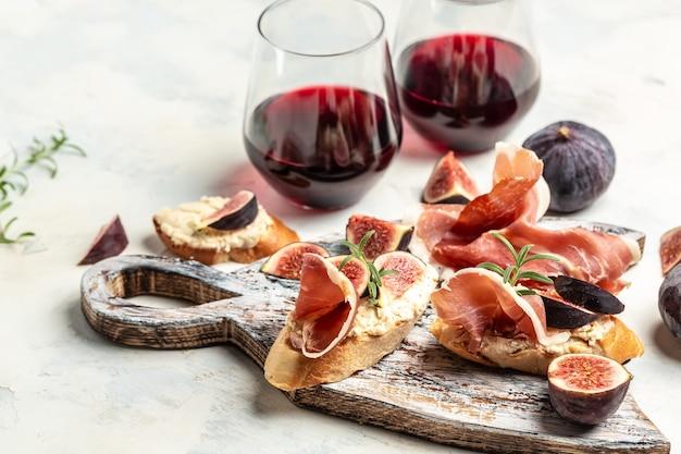 Crostini au prosciutto, fromage à la crème et figues. bruschetta traditionnelle avec jambon de parme séché et prosciutto. antipasti au vin rouge. vue de dessus.