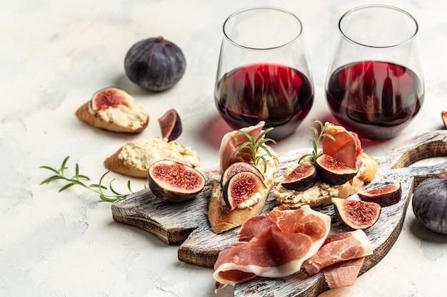 Crostini au prosciutto, fromage à la crème, figues. tapas espagnols traditionnels mis antipasti au vin rouge. bannière, recette de menu. vue de dessus