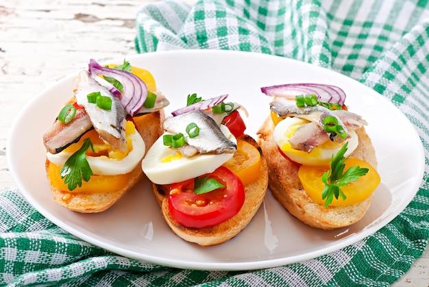 Crostini aux anchois, tomates et oeuf, décoré de verts