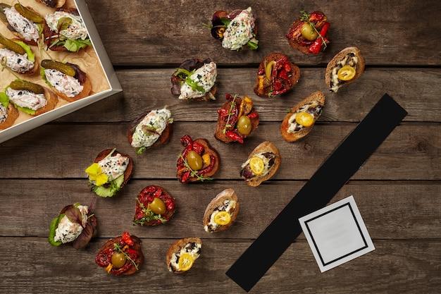 Crostini sur pain grillé avec garnitures en carton sur fond de bois