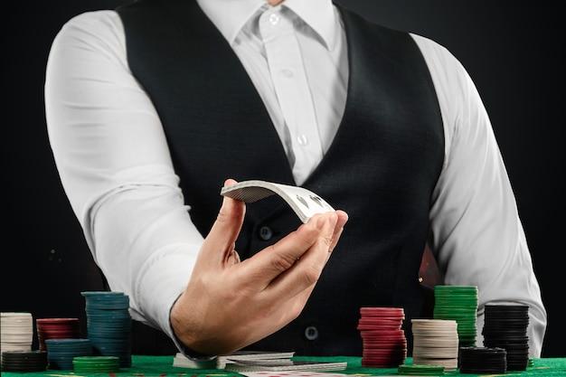 Croupier mâle dans le casino à la table les mains en gros plan. concept de casino, jeux de hasard, poker, jetons sur la table verte du casino.