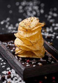 Croustillant de chips de chips de pommes de terre au poivre délicieux snack sur planche de bois foncé et sel