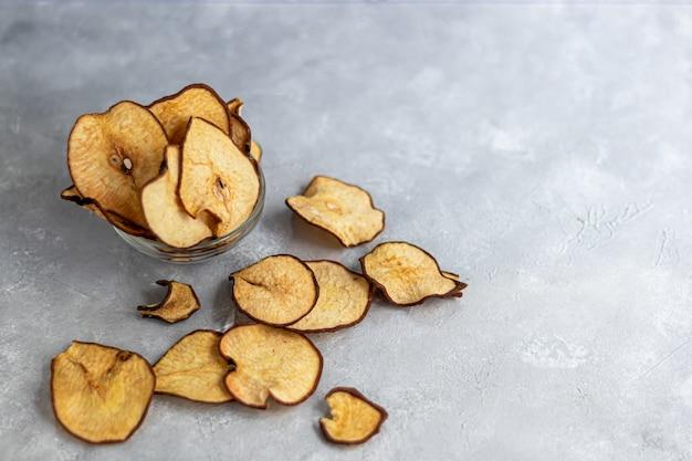 Croustillant de croustilles de poire sur une table grise. dans le tableau sont des poires mûres. nourriture saine, décor.