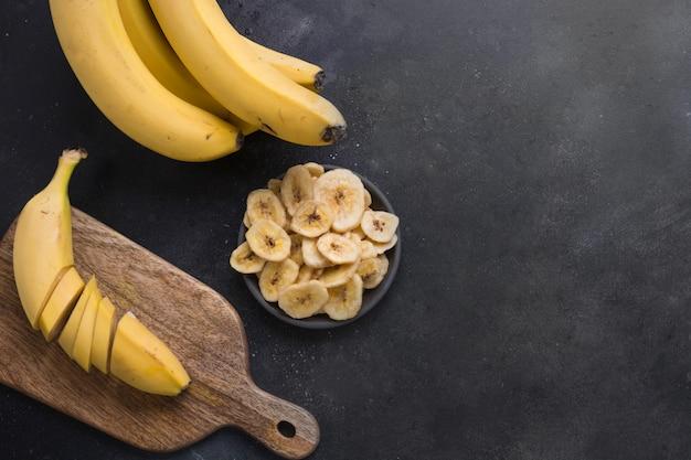 Croustilles de banane déshydratées et séchées sur fond noir