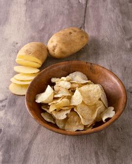 Croustilles sur un bol avec pommes de terre crues